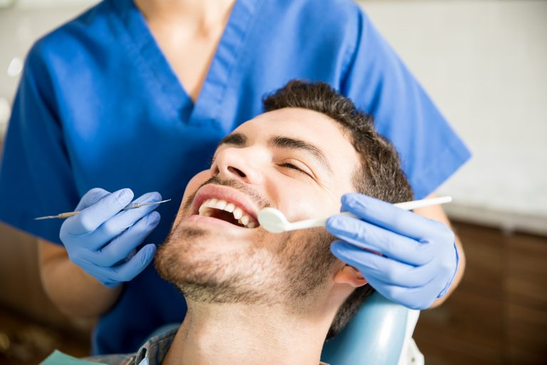 Man Receiving Treatment From Dentist In Dental Clinic