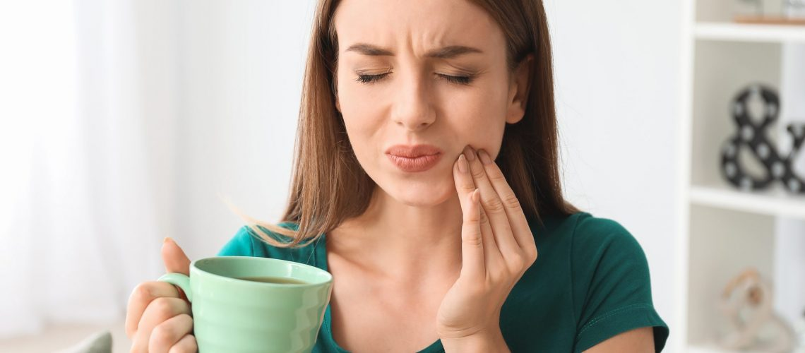 Young Woman With Sensitive Teeth And Cup Of Hot Coffee At Home